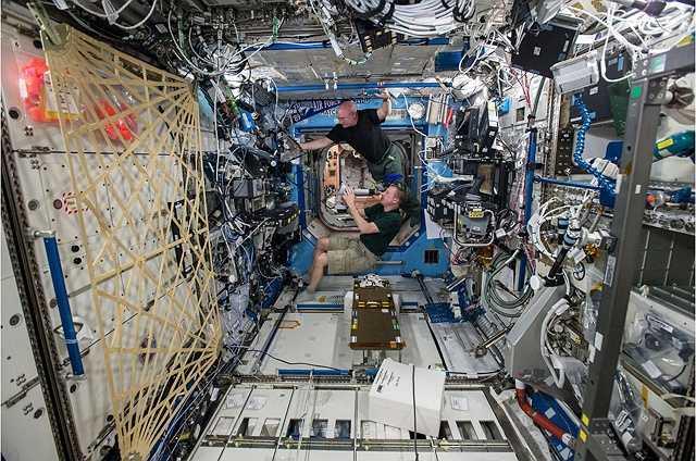 2 phi hành gia đang thực hiện bài kiểm tra mắt, đây là việc phải làm thường xuyên bởi khi ở lâu ngoài không gian tầm nhìn sẽ  bị giảm sút.