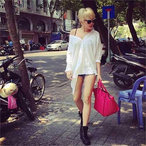 Tóc Tiên nổi bật trên phố với sơ mi trắng kéo lệch vai và sooc ngắn.