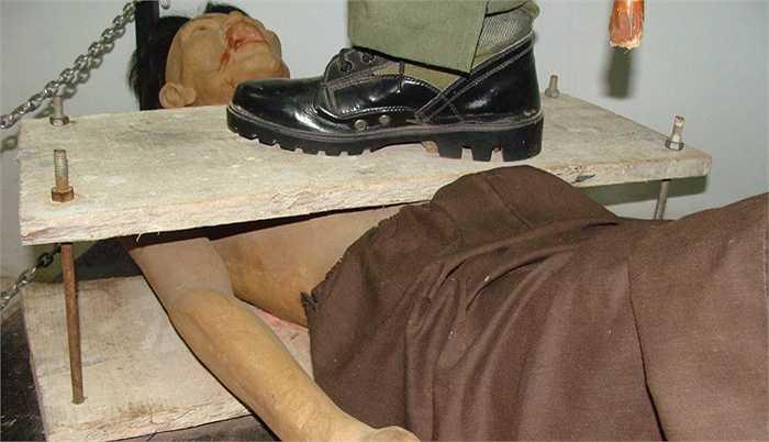 Bọn cai ngục dùng 2 tấm ván ép vào ngực và lưng tù nhân, rồi xiết bù loong hai đầu làm tù nhân vỡ lồng ngực, vỡ tim, tắt thở.