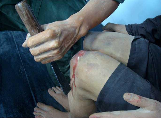 Bọn cai ngục dùng chiếc đục bằng sắt, thứ mà thợ mộc dùng, đặt vào đầu gối, rồi dùng búa gỗ gõ mạnh, khiến đục xuyên vào chân, đánh bật xương bánh chè ra ngoài. Cách tra tấn này khiến nhiều tù nhân bại liệt suốt đời.