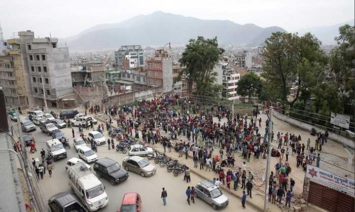 Người dân tụ tập trên một quảng trường rộng, nhằm tránh những cơn dư chấn có thể làm các tòa nhà đổ thêm xuống đầu họ. Ảnh: Narendra Shrestha/EPA