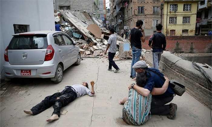 Một người đàn ông dường như bị gãy chân, nằm la hét trên mặt đất trong khi chờ cáng y tế. Ảnh: Narendra Shrestha/EPA