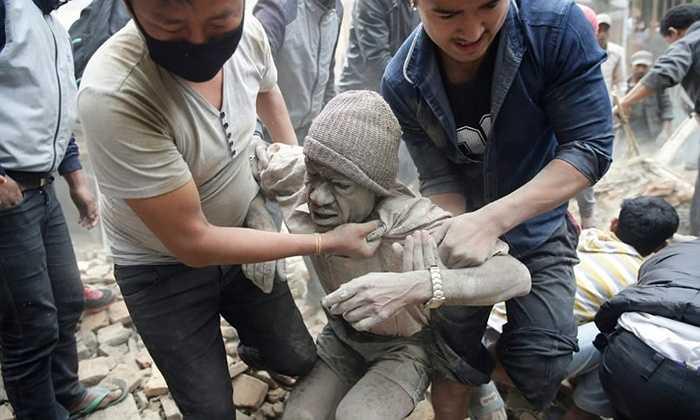 Bị vùi lấp trong đống vôi vữa, người đàn ông này may mắn được cứu thoát. Ảnh: Narendra Shrestha/EPA