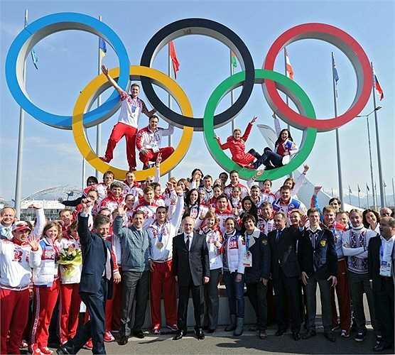 Tổng thống Nga Vladimir Putin (ở giữa) chụp ảnh cùng những vận động viên chiến thắng trong Olympic Winter Games XXII tại Sochi ngày 24/2/2014.
