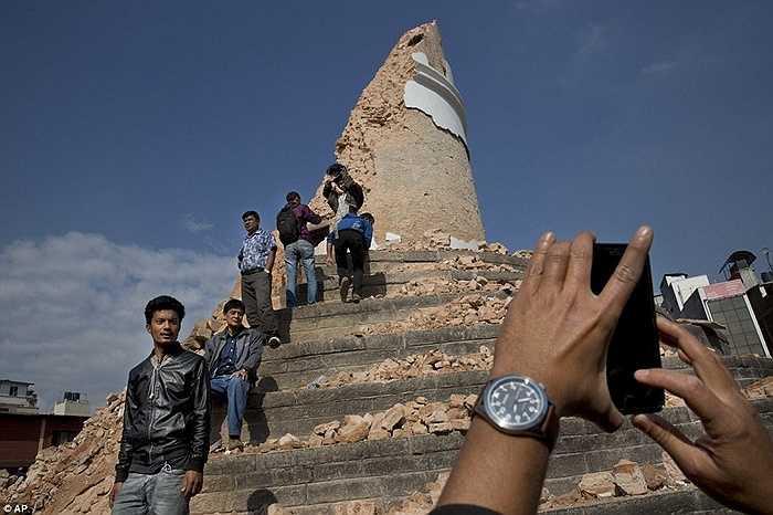 Một người đàn ông còn đang nhờ bạn chụp lại cho mình một bức ảnh thật 'hoành tráng' với phần còn lại của tòa tháp cao nhất đã bị sụp đổ của người Nepal.