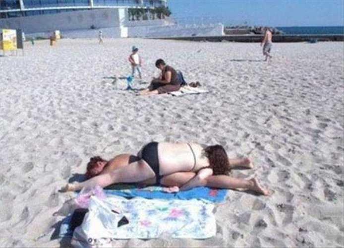 Hai phụ nữ nằm chồng lên nhau ngủ say sưa trên bãi biển