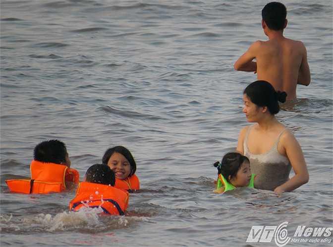 Trẻ em được phụ huynh đưa đi tắm biển, được trang bị áo phao cứu sinh và có sự giám sát của người lớn
