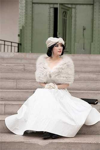 Chiếc váy màu trắng của thương hiệu Maticevski kết hợp cùng khăn lông, găng tay kiểu cách của Elcom Fur.