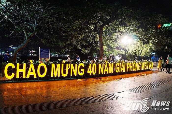 Đèn biểu ngữ 'Chào mừng 40 năm giải phóng miền Nam' màu vàng nổi bật được đặt ngay tại trung tâm của bờ Hồ Hoàn Kiếm.