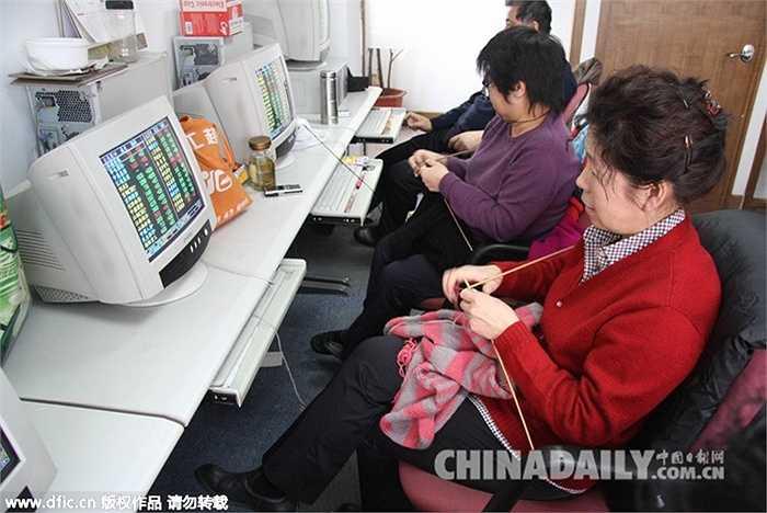 Ảnh chụp ngày 23/2/2010, các nhà đầu tư nữ vừa tranh thủ ngồi xem màn hình máy tính sự lên xuống của các chỉ số vừa đan áo len tại một sàn chứng khoán ở Thiên Tân