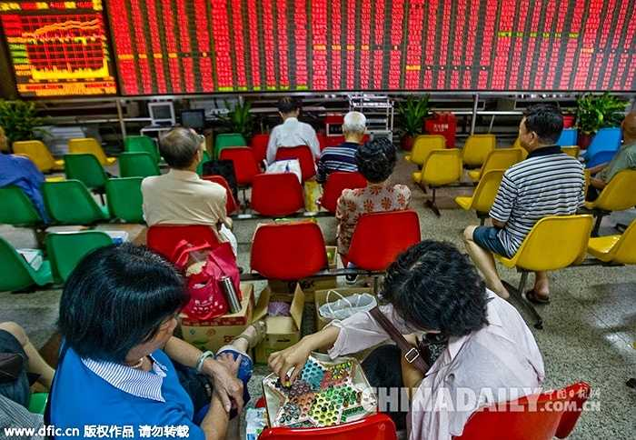 Ảnh chụp ngày 30/8/2010, các nhà đầu tư tranh thủ chơi trò chơi lúc rảnh rỗi ngay tại sàn chứng khoán ở Phật Sơn (Trung Quốc)