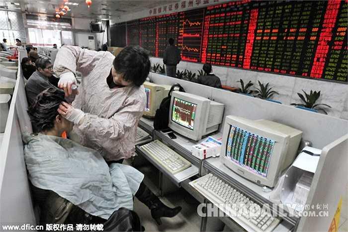 Ảnh chụp ngày 9/12/2010, một nhà đầu tư đang nhuộm tóc cho một nhà đầu tư khác ngay tại sàn chứng khoán
