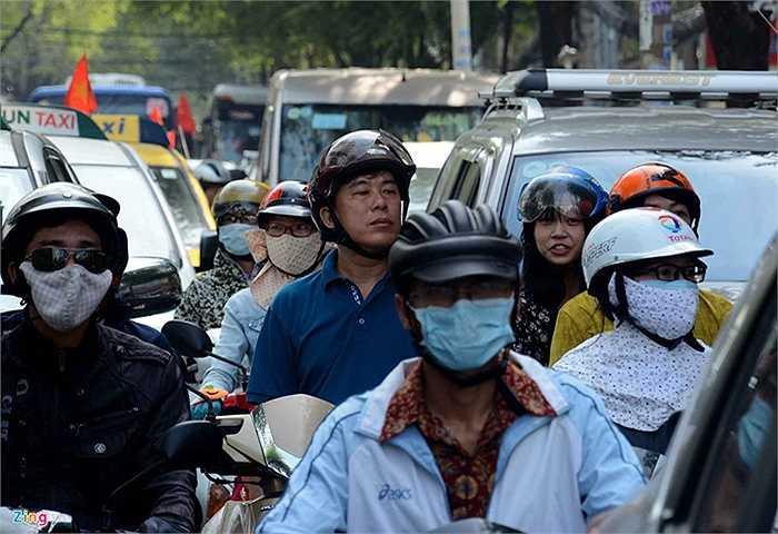 Nhiều người sốt ruột ngồi trên xe máy chống chân xuống đất hướng mắt nhìn ra xa ngóng đợi.