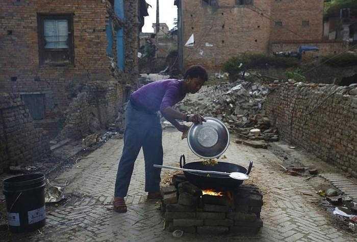 Một người đàn ông đang nấu ăn gần ngôi nhà bị đổ sập của mình.