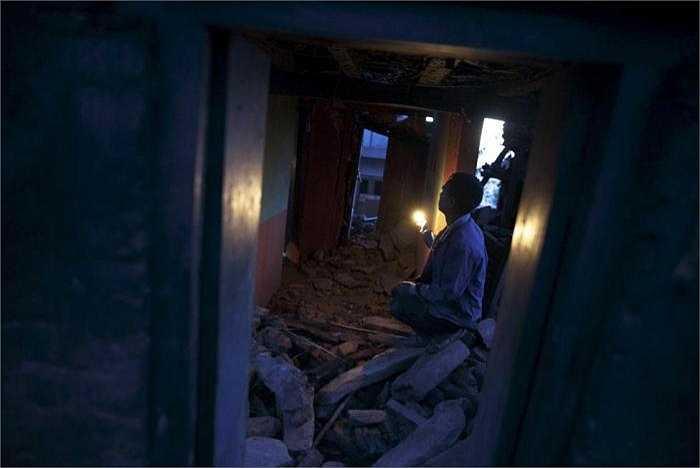 Một người đàn ông đang dùng đèn để tìm lại những vật dụng còn có thể dùng được trong căn nhà đổ nát sau trận động đất kinh hoàng (Minh Chiến/ Theo Reuters)