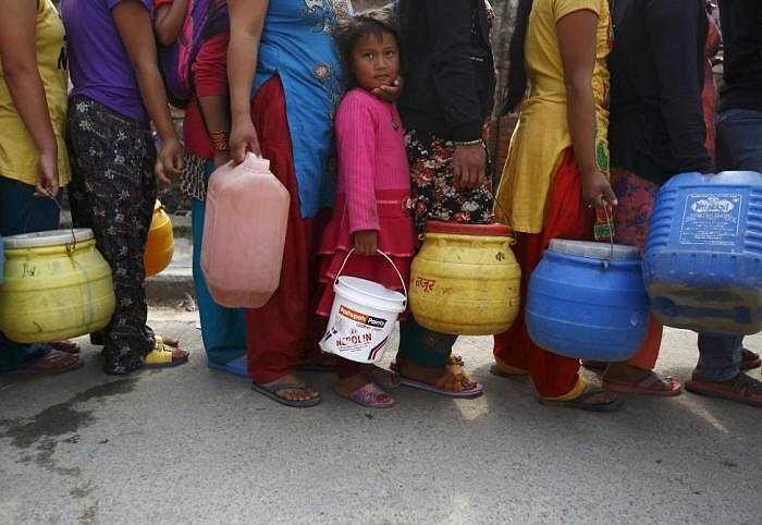 Một bé gái xếp hàng đợi lấy nước gần nhà tạm ở Kathmandu, Nepal.