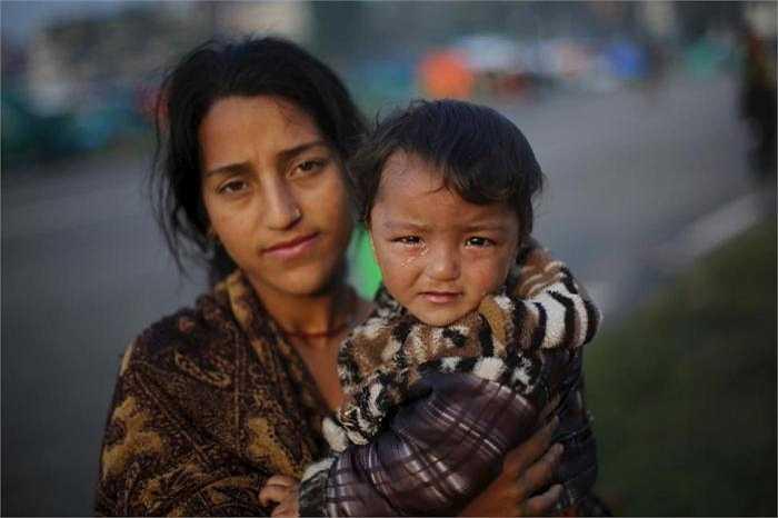 Một phụ nữ Nepla ôm con trai đứng bên ngoài khu nhà tạm sau trận động đất kinh hoàng.