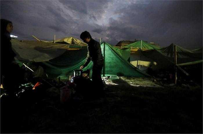 Một cậu bé chuẩn bị nấu thức ăn tại khu lều tạm nằm trên bãi đất trống, cuộc sống đang rất khó khăn với người dân Nepal.