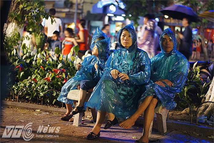 Trời trở mưa nặng hạt nhưng vẫn có rất đông người tập trung tại khu vực bờ hồ Hoàn Kiếm để chờ xem pháo hoa.