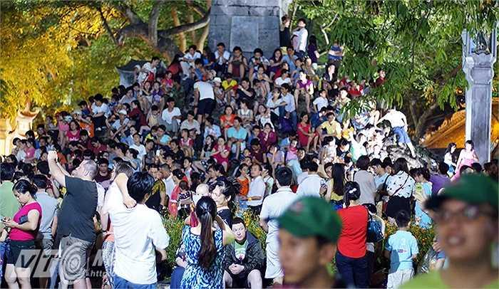 Người dân ngồi kín xung quanh chân tháp Bút chờ xem bắn pháo hoa.