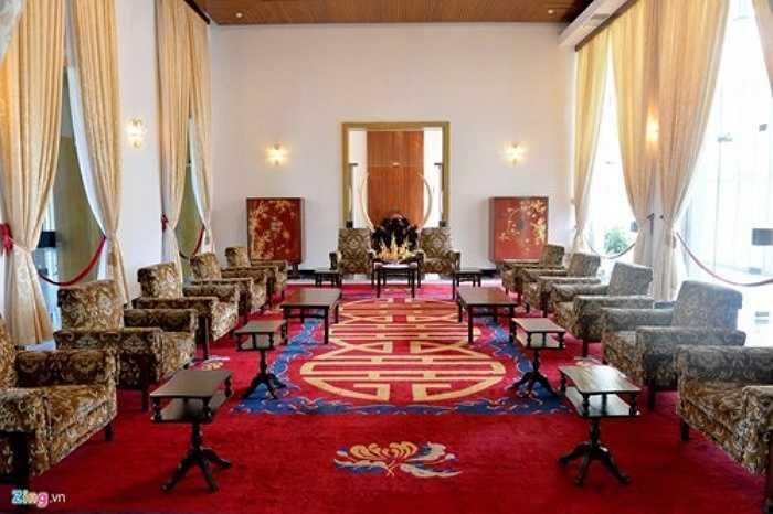 Phòng tiếp khách trải thảm thêu hoa cúc và chữ song hỷ cùng với bức bình phong ngà voi lớn. Hai bên có tủ nhỏ trạm trổ trúc mai.