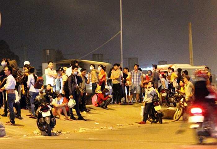 Tại TP.HCM, hàng trăm người dân đứng ngồi trên QL1 (đoạn trước KDL Suối Tiên, quận 9) với lỉnh kỉnh hành lý dõi mắt trông từng chuyến xe khách để về quê nghỉ lễ trong đêm 27/4. – (Ảnh: Kiến thức)