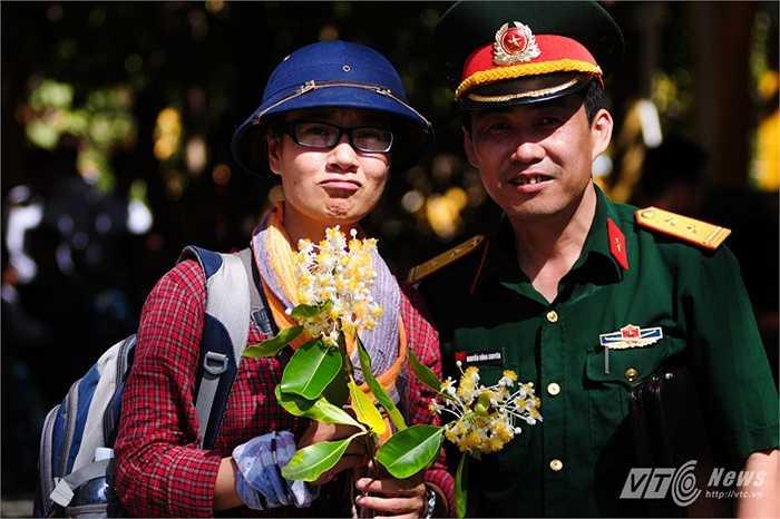 Nữ cán bộ đoàn công tác chụp ảnh cùng sỹ quan quân đội bên cành hoa mù u trắng được các chiến sỹ tặng làm kỷ niệm (Tùng Đinh/Thực hiện)