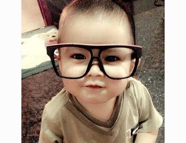 Cậu bé có gương mặt bụ bẫm đáng yêu, làn da trắng hồng và đôi mắt đen láy.