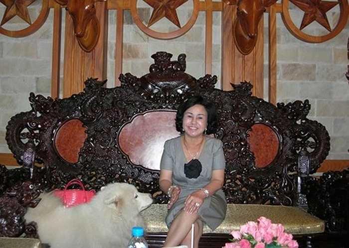 Bà Diệu Hiền bên bộ ghế gỗ hoành tráng, đắt tiền tại căn biệt thự.