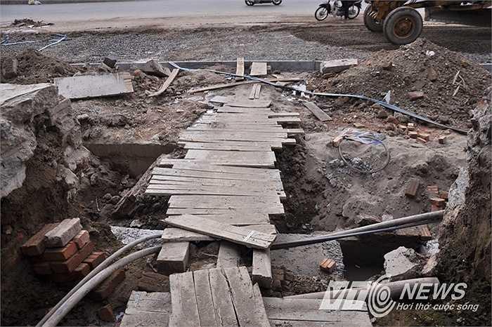 Do vỉa hè, đường thoát nước đang thi công, người dân phải bắc cầu gỗ để vào nhà.