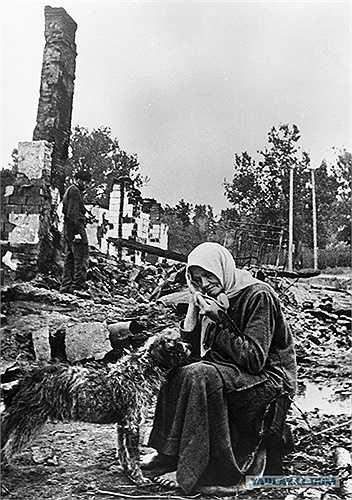 Người phụ nữ ngồi bên cạnh ngôi nhà đã bị phá hủy bởi Đức Quốc xã