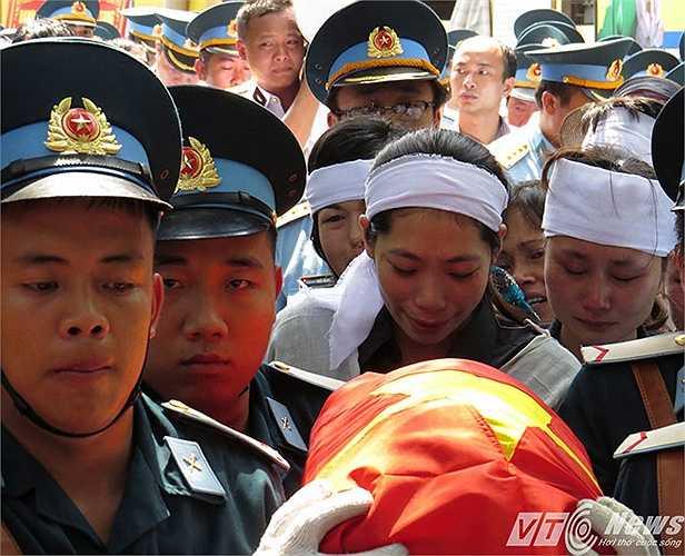 Chị Nguyễn Thị Oanh (vợ thiếu tá Anh Tú) đau đớn như không thể đứng vững, phải có người thân dìu theo sau di cốt chồng.