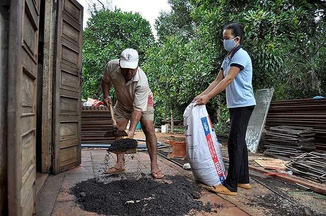 Sau khi đốt, ông Chung cho xác côn trùng vào bao tải rồi mang đi đổ.