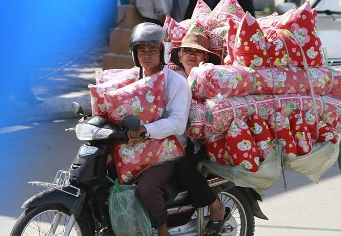 Một chiếc xe nhỏ, 2 người lớn, chỉ 1 chiếc mũ bảo hiểm và cả đống gối chở phía sau tại Campuchia
