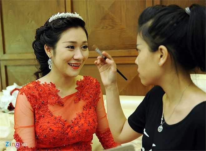 Cô dâu Minh Nguyệt được chuyên viên trang điểm chăm sóc trước giờ cử hành hôn lễ. Tân nương chọn cho mình mẫu váy cưới hoa ren màu đỏ quyến rũ.