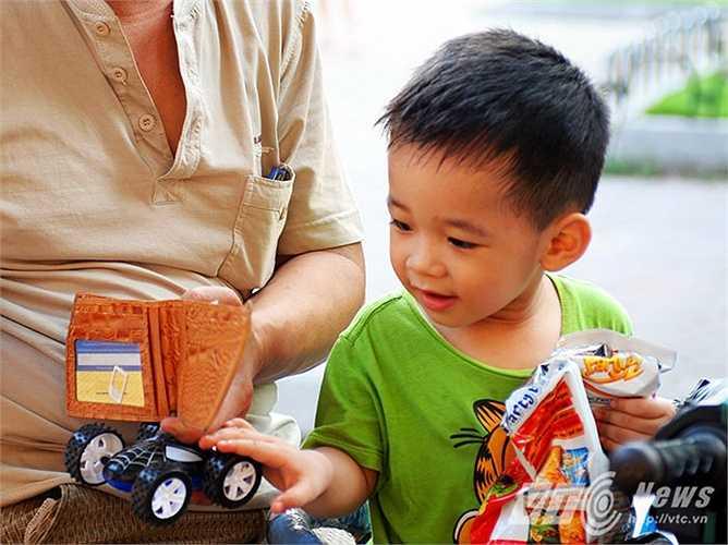 Vẻ hào hứng của một em nhỏ khi được cha mẹ mua cho món đồ chơi thú vị từ sạp hàng rong của David.
