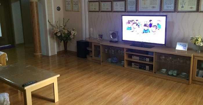 Phòng khách được lát gỗ, có tivi