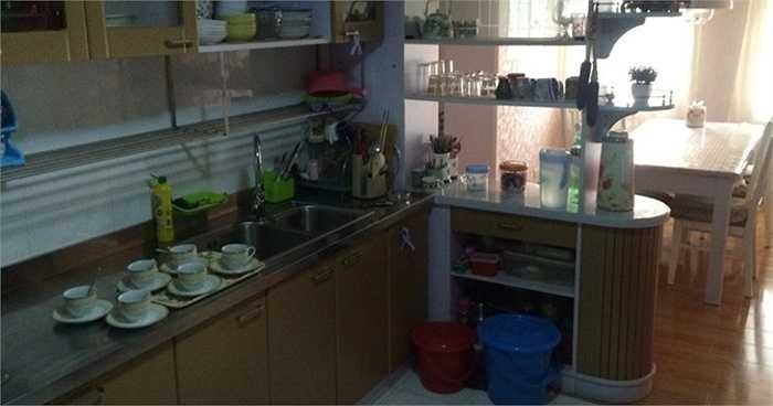 Căn bếp có bồn rửa đôi, dàn để bát đĩa bằng kim loại phủ sơn. Bàn ăn tràn ngập ánh sáng tự nhiên
