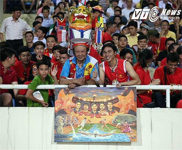 Họa sĩ An Thắng (phải) và bức tranh mới nhất cổ vũ U23 Việt Nam (Ảnh: Nhạc Dương)