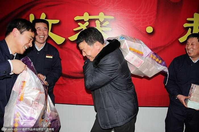 Một công ty bất động sản ở thành phố Thương Khâu, tỉnh Hà Nam đã chi 11 triệu nhân dân tệ làm tiền thưởng tết cho nhân viên vào năm ngoái. Trong ảnh là một nhân viên công ty vác bao tải đựng 2 triệu tệ tiền thưởng Tết.