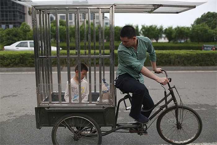 Cậu bé 10 tuổi ở thành phố Đài Châu, tỉnh Chiết Giang, Trung Quốc được bố đặt trong lồng sắt đi dạo phố