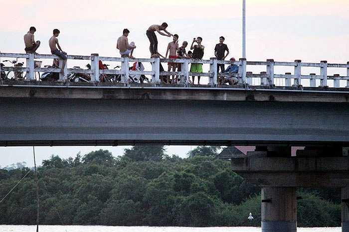 Ban đầu, có 2 người tới trước, sau cuộc điện thoại 'thúc giục' bạn bè. Chừng 15 phút, có từ 5 -10 người nữa tới. Nhóm thanh niên này trèo lên thành cầu có độ cao chừng 15 – 20 mét rồi nhảy xuống giữa sông.