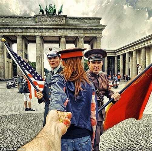 Đôi vợ chồng chụp ảnh với những diễn viên ăn mặc như những người lính thời kỳ chiến tranh lạnh bên ngoài cổng Brandenburg ở Berlin, Đức.