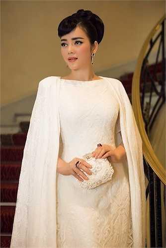 Cô diện trang phục ren trắng với áo choàng, phụ kiện và cách trang điểm, làm tóc theo phong cách quý tộc.