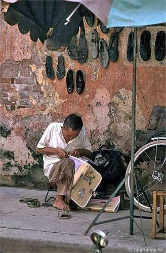 Thợ sửa đồ da tại một góc vỉa hè.