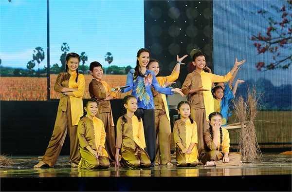 Sau đó, các bé nhỏ trong team The Voice Kids xuất hiện cùng cô giáo Cẩm Ly và 2 cô con gái xinh xắn của mình tham gia trong điệu múa Lâm Thol Trà Vinh rộn ràng và trình diễn bài Gánh lúa.