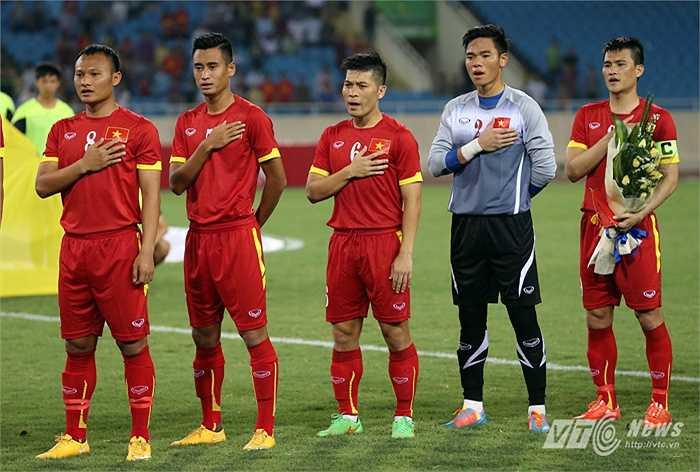 Các cầu thủ Việt Nam nghiêm trang khi thực hiện nghi thức chào cờ. (Ảnh: Quang Minh)