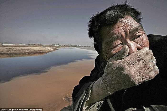 Một chàng chăn cừu bên sông Hoàng Hà không thể chịu được mùi thôi tại khu vực Nội Mông, Trung Quốc