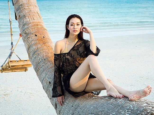 Khánh My khoe dáng bên bãi biển vắng với bikini và áo lưới khoác ngoài.