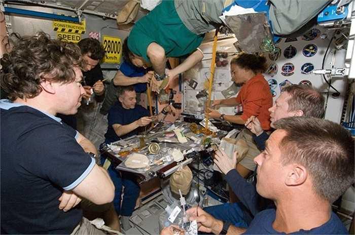 Quang cảnh chuẩn bị bữa ăn trên tàu vũ trụ. Mọi người tập trung xung quanh bàn ăn, nhưng không ngồi được mà ai cũng lơ lửng